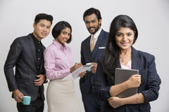 Happy Businesswoman holding tablet with her colleagues. Cheerful businesswoman holding tablet with her colleagues on white background Stock Images