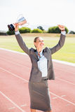Happy businesswoman holding up a trophy Stock Photography