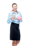 Happy businesswoman holds piggy bank and dollars on white Stock Image