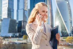 Happy businesswoman in jacket talking on cell phone. Urban background Royalty Free Stock Photography