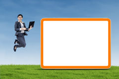 Happy businesswoman jumping and holding a notebook Stock Images