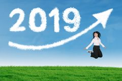 Happy businesswoman is jumping with number 2019 royalty free stock photography