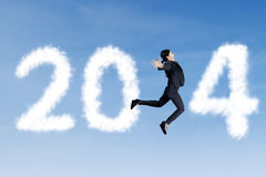 Happy businesswoman jumps with clouds of 2014. Happy asian businesswoman is jumping with clouds of 2014 Royalty Free Stock Image