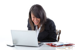 Happy businesswoman with laptop. Attractive young businesswoman laughing at screen on open laptop; white studio background Stock Photography