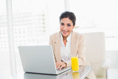 Happy businesswoman with laptop and glass of orange juice at desk Royalty Free Stock Photography