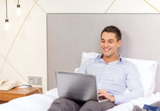 Happy businesswoman with laptop in hotel room Stock Photos