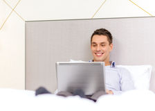Happy businesswoman with laptop in hotel room Stock Images