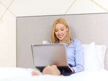 Happy businesswoman with laptop in hotel room Royalty Free Stock Images