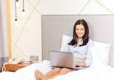 Happy businesswoman with laptop in hotel room Royalty Free Stock Photos