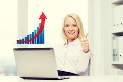 Happy businesswoman with laptop showing thumbs up Stock Image