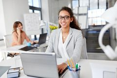 Happy businesswoman with laptop working at office Stock Photo