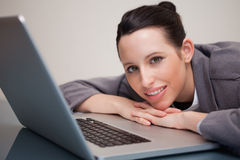 Happy businesswoman leaning against her laptop Stock Image