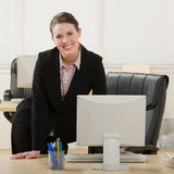 Happy businesswoman leaning on desk Stock Photos