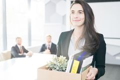 Happy Businesswoman Leaving Job. Waist up portrait of smiling young businesswoman holding box of personal belongings leaving office after quitting job, copy royalty free stock images