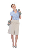 Happy businesswoman lifting dumbbells looking at camera Stock Photography