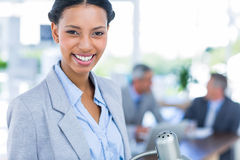 Happy businesswoman looking at camera with her colleagues behind her Stock Photography