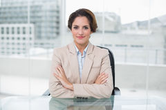 Happy businesswoman looking at camera at her desk with arms crossed Royalty Free Stock Photography