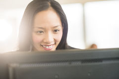 Happy Businesswoman Looking At Computer. Close-up of happy mid adult businesswoman looking at computer in office Stock Image