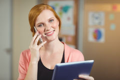 Happy businesswoman looking at digital tablet while talking on phone Royalty Free Stock Image