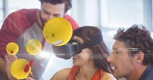 Happy businesswoman looking at emojis on VR glasses by colleagues. Digital composite of Happy businesswoman looking at emojis on VR glasses by colleagues Stock Photography