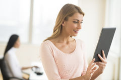 Happy Businesswoman Looking At Touchpad In Office Stock Image