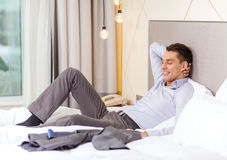 Happy businesswoman lying in bed in hotel room Royalty Free Stock Images