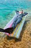 Happy businesswoman lying in flippers and goggles. Happy young Caucasian businesswoman wearing suit, flippers and swimming goggles lying on pool raft in water Royalty Free Stock Image