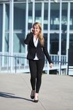 Happy businesswoman on the mobile phone walking on the street Stock Photography