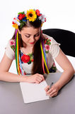 Happy businesswoman with note and pen by a desk.In the Ukrainian national costume Stock Images