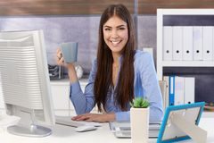 Happy businesswoman in office with coffee Royalty Free Stock Photos