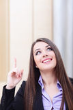Happy businesswoman in office pointing up Stock Photography