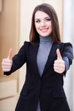 Happy businesswoman in office with thumbs up Stock Photo
