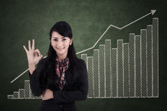 Happy businesswoman with ok sign on profit bar chart Stock Photos