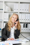 Happy Businesswoman On Phone At Her Desk Stock Images