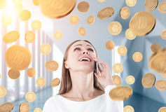 Happy businesswoman on phone looking up, coin rain. Portrait of a happy young and beautiful businesswoman talking on a smartphone and looking upwards. She is Royalty Free Stock Images