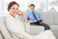Happy businesswoman on the phone sitting on couch Stock Photography