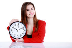 Happy businesswoman pointing on a clock. Beautiful girl posing in a red jacket on a white background Royalty Free Stock Photos