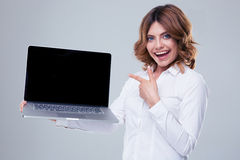Happy businesswoman pointing finger on laptop screen Stock Image