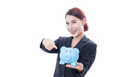 Happy businesswoman pointing at piggy bank Royalty Free Stock Photo