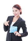 Happy businesswoman pointing at piggy bank Stock Photos