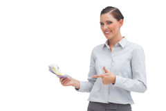 Happy businesswoman pointing to money in her hand Stock Photo