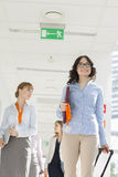 Happy businesswoman pulling luggage while walking with team at airport Stock Images