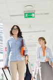 Happy businesswoman pulling luggage while walking with team at airport Royalty Free Stock Photography