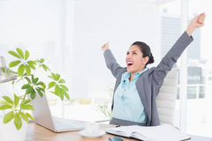 Happy businesswoman with raised arms. In her office Stock Photo