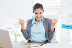 Happy businesswoman with raised arms. In her office Stock Photos
