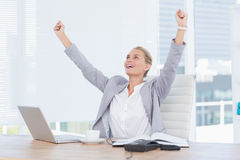 Happy businesswoman with raised arms. In her office Royalty Free Stock Photo