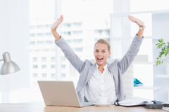 Happy businesswoman with raised arms. In her office Royalty Free Stock Photos