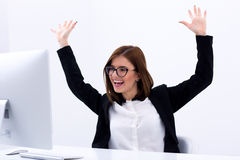 Happy businesswoman with raised hands up Stock Photo