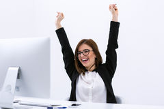 Happy businesswoman with raised hands up. Portrait of a happy businesswoman with raised hands up and looking on PC Royalty Free Stock Photography