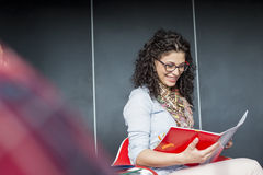 Happy businesswoman reading book in office Royalty Free Stock Image